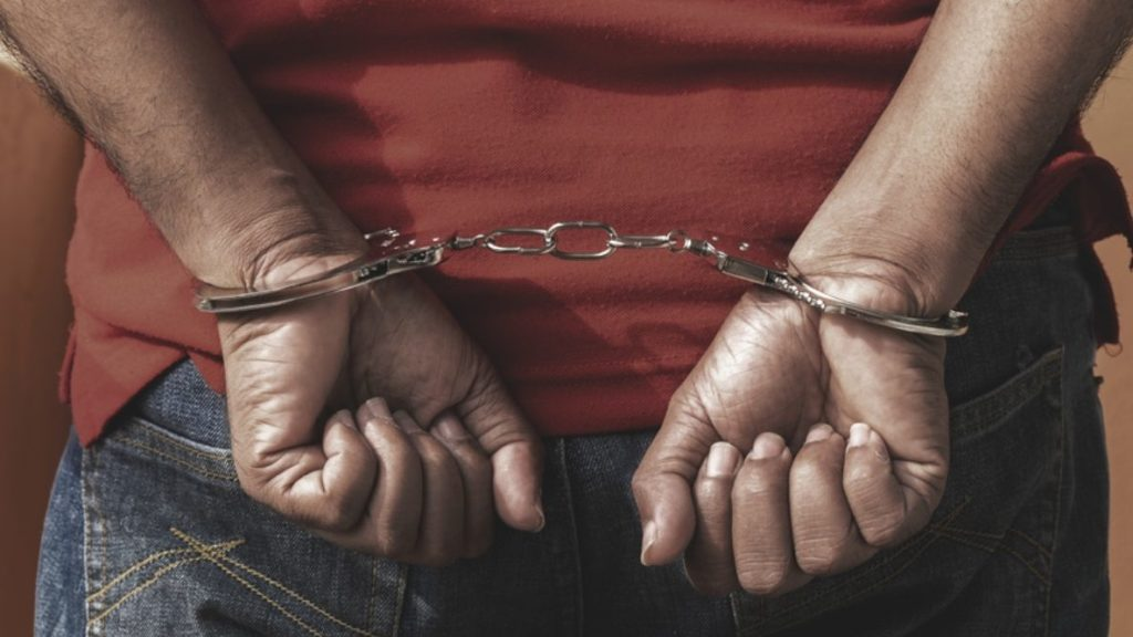 a young person's hands balled into fists, shackled in handcuffs